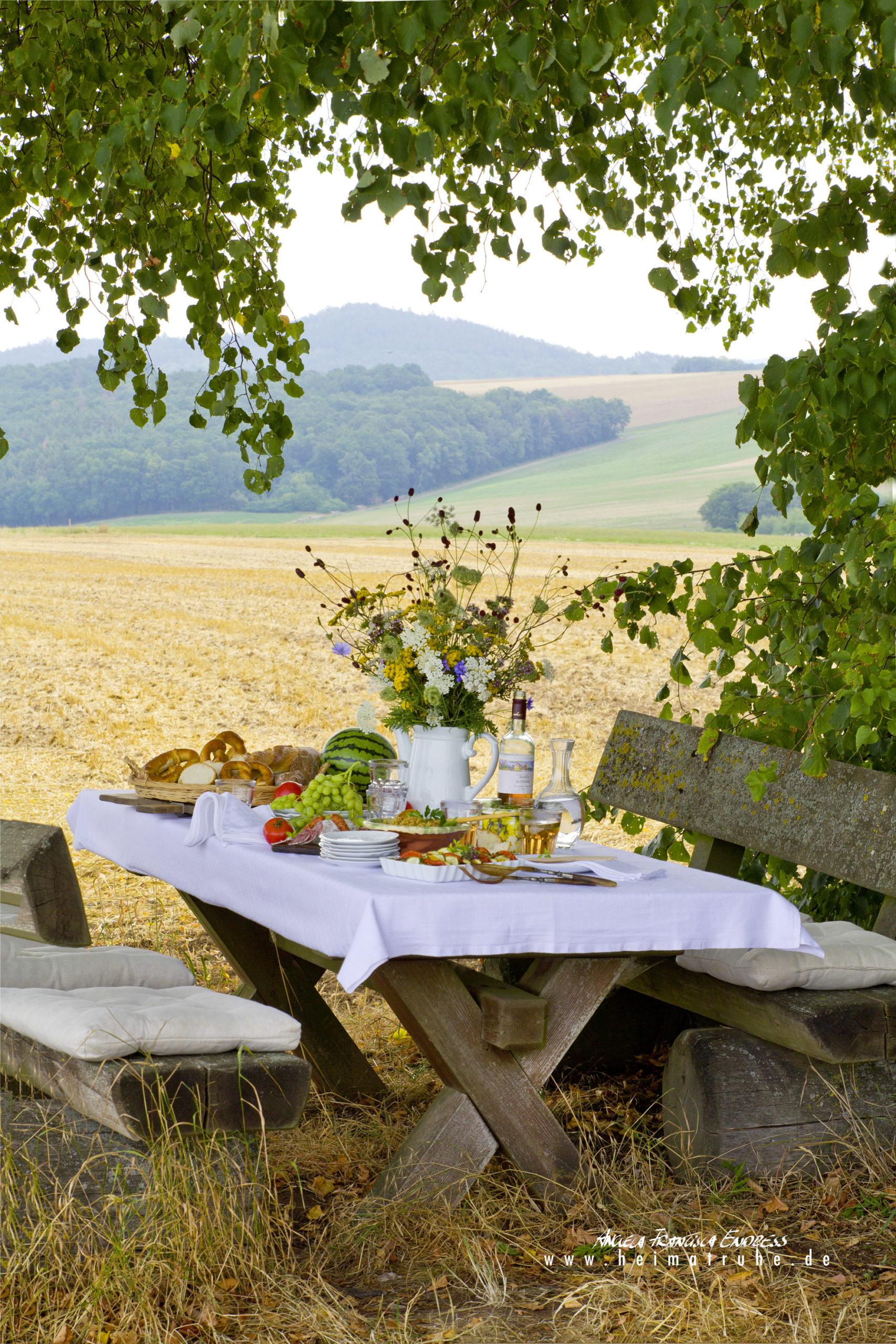 gedeckter Tisch mit Wiesenblumen am Feldrand in fränkischer Landschaft