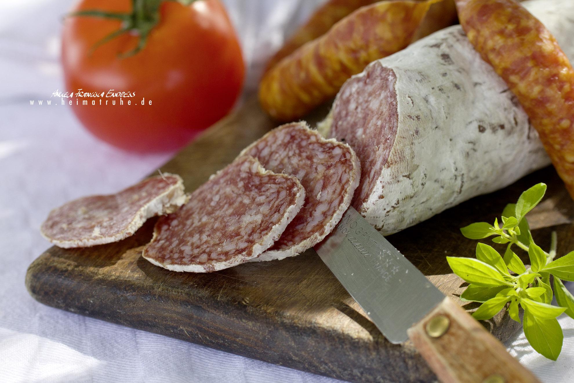 Salami wird in Scheiben geschnitten, Tomate