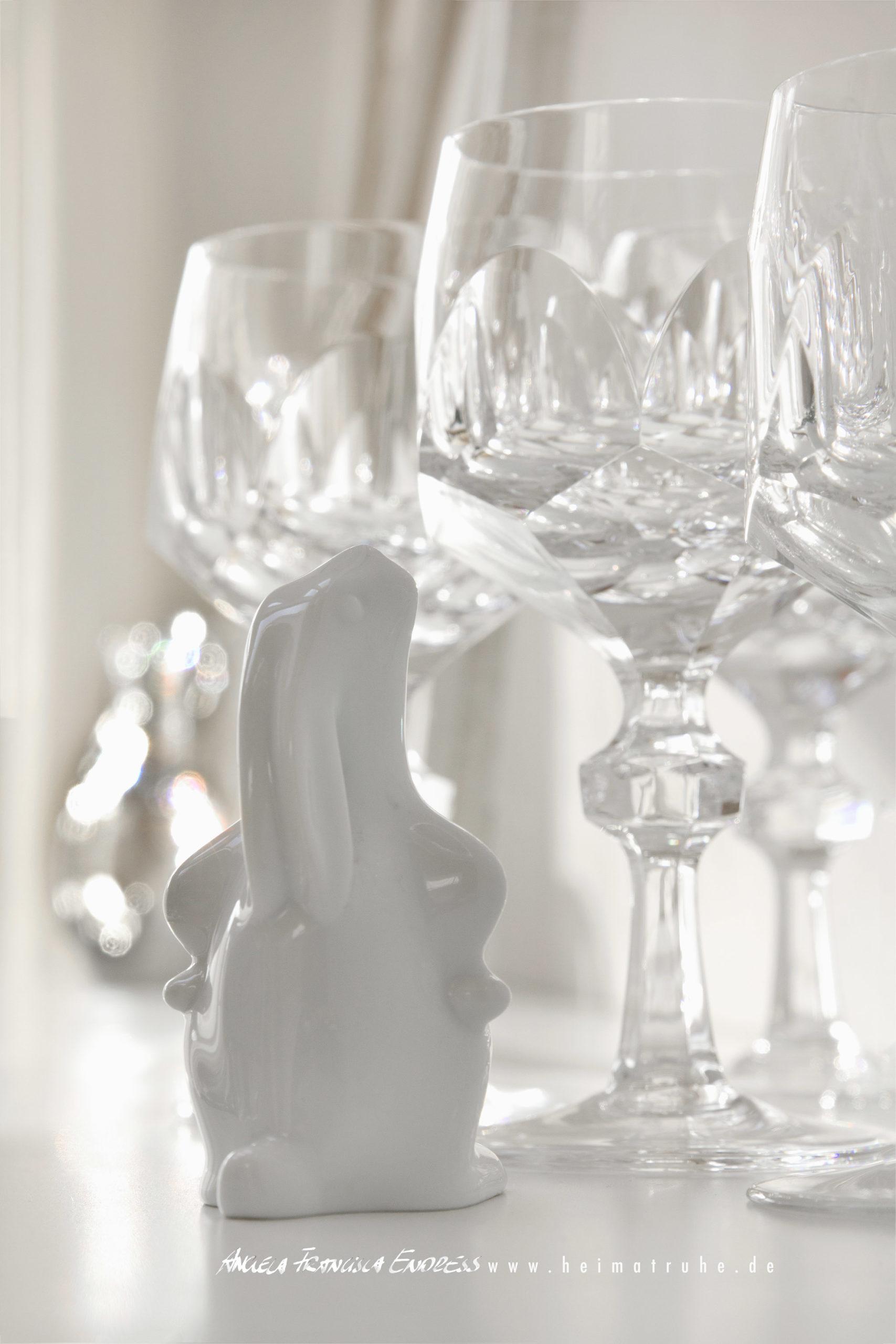 Porzellan Osterhase schaut sich Kristallgläser an