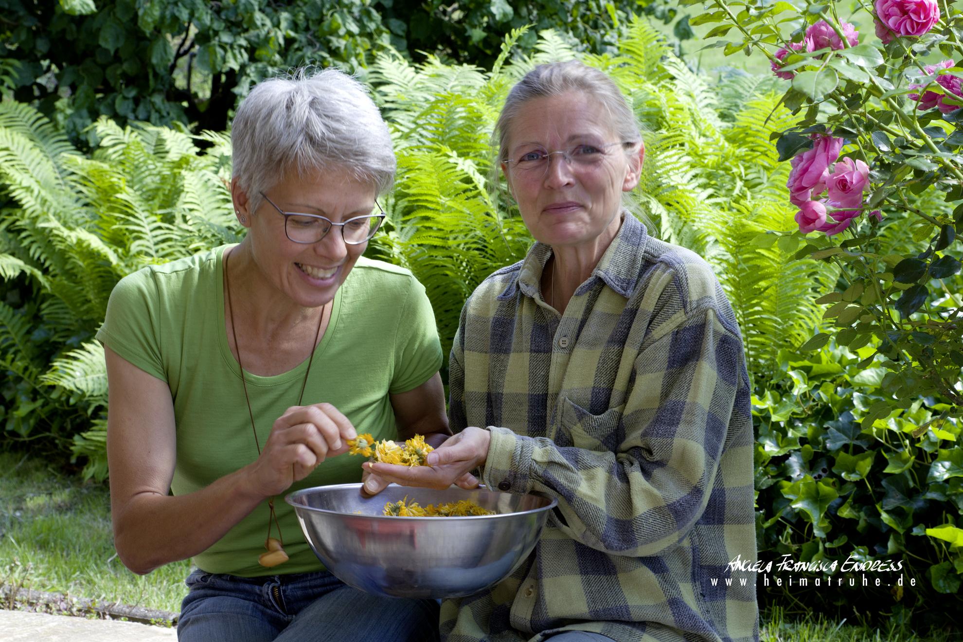 """Ute Kern und Monika Rehs (von liunks) im Garten ihrer """"Berglandkräuter"""" mit Calendula-Blüten"""