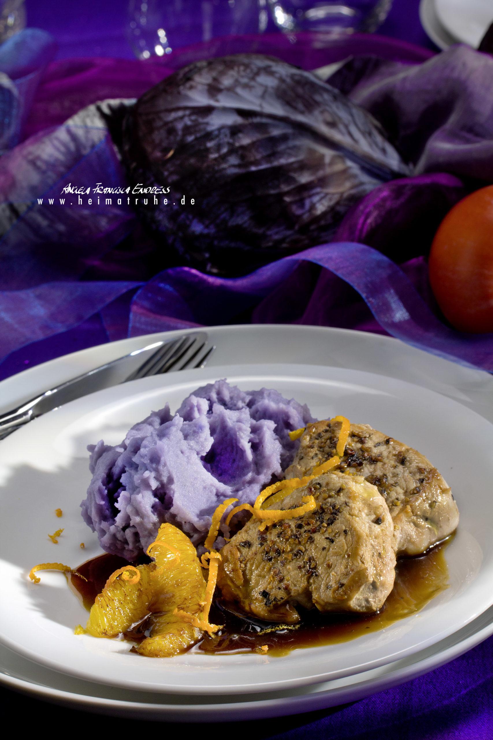 Teller mit gefeffertenSchweine-Medaillons und Tischdeko in lila mit Kaki-Früchten