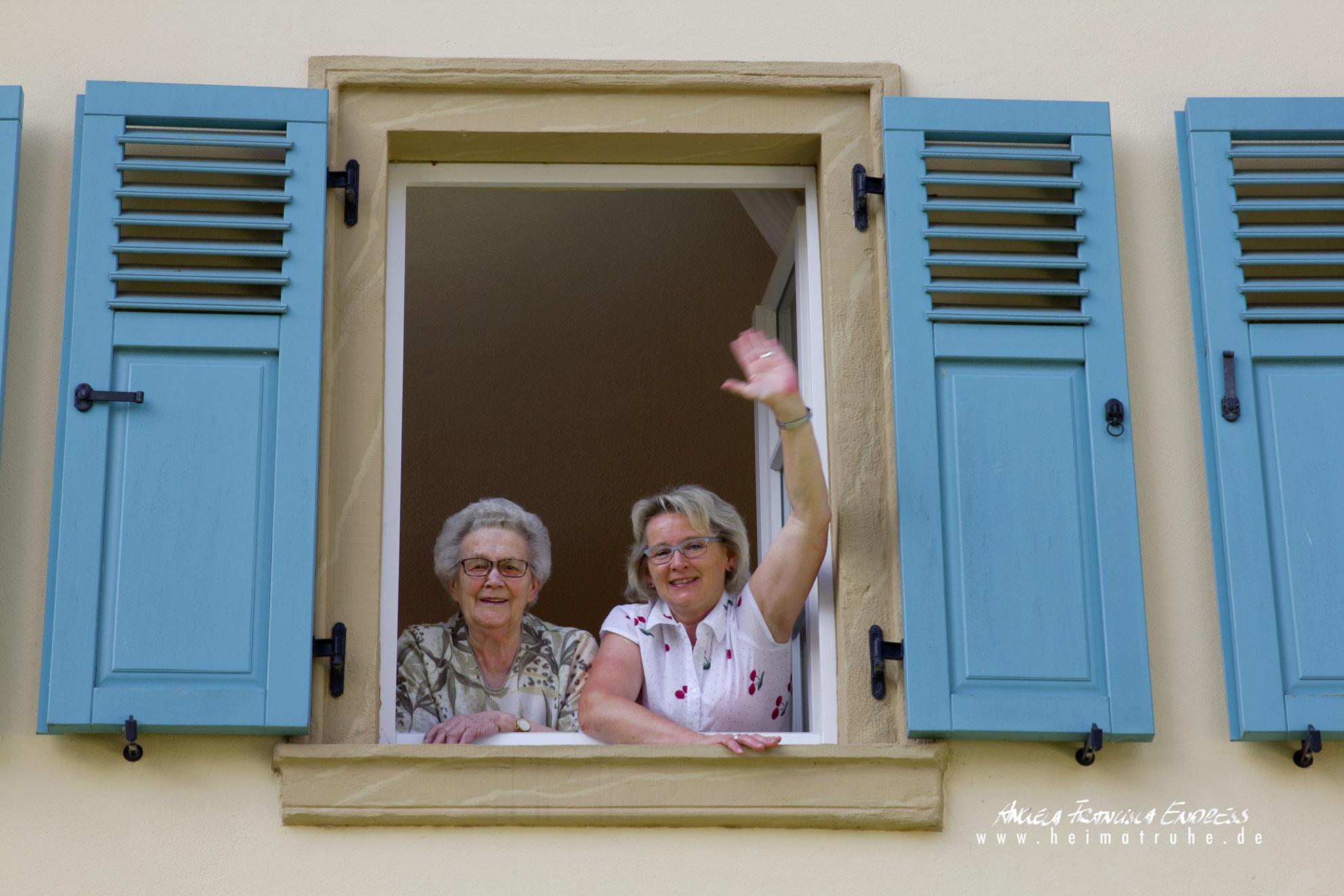 Adelgunde und Oma Resi winken aus dem Fenster