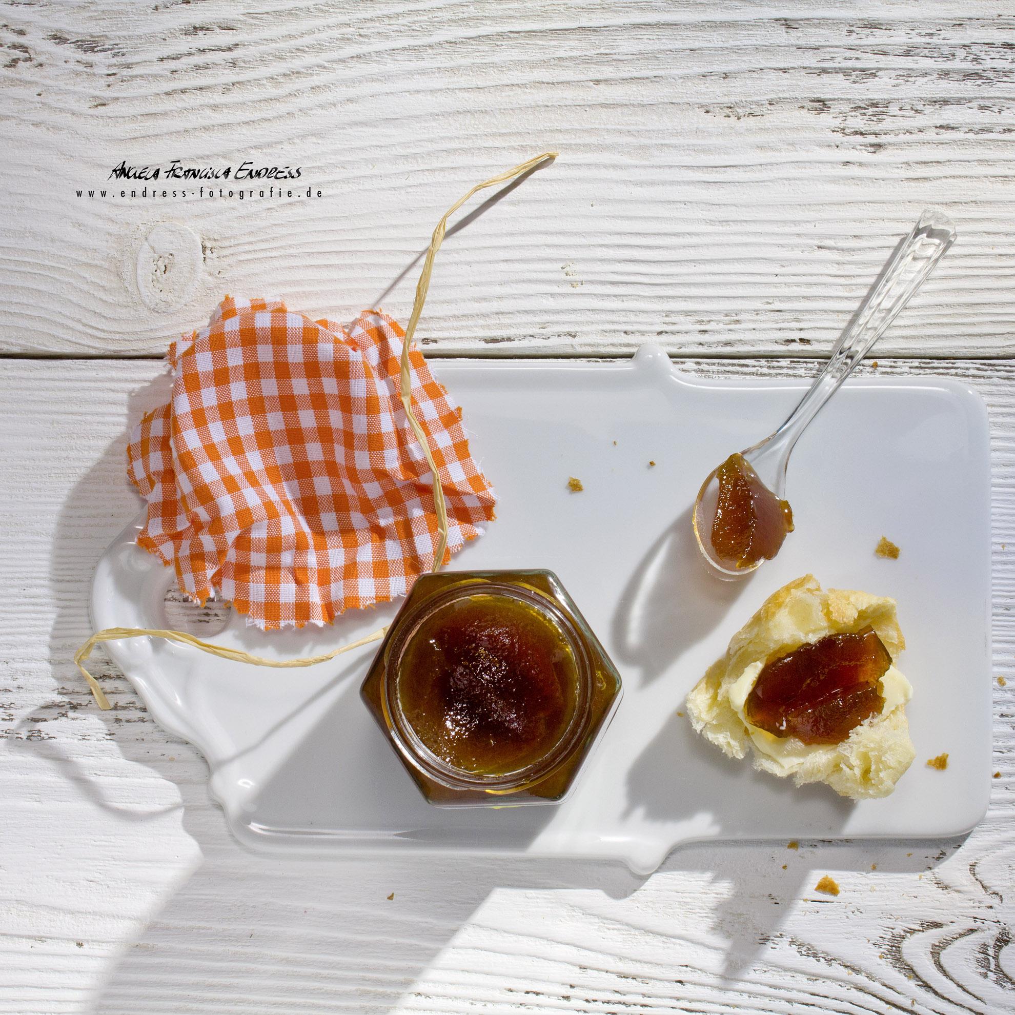 Renecloden-Marmelade, Marmeladen-Glas auf Porzellanbrettchen mit Brötchenstück, Butter und Marmelade