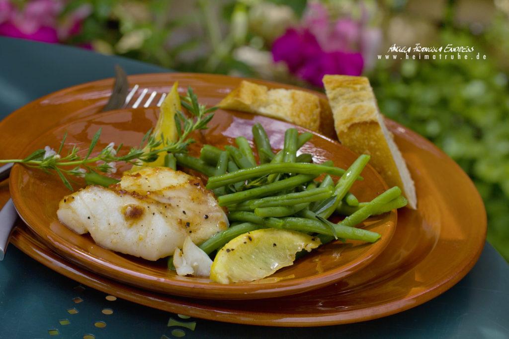 Fischfilet, glasiert mit Bohnen, Zitronenschnitzen, Rezept Foto